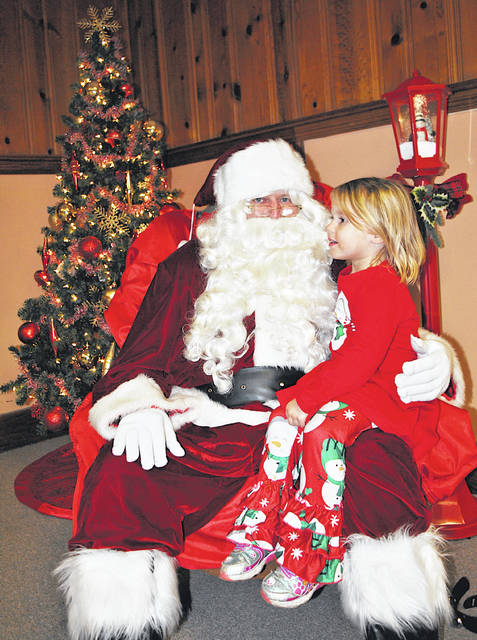 Three-year-old Hillsboro resident Scarlett Hallowell gives her wish list to Santa Claus in The Times-Gazette offices following the annual Hillsboro Lighted Christmas Parade presented by the Hillsboro Uptown Business Association with approval of the City of Hillsboro.