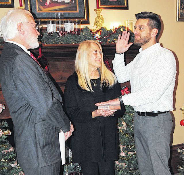With his mother, Deborah Harsha, holding the Bible, incoming Hillsboro Mayor Justin Harsha, right, is sworn in Wednesday by retired Appellate Judge William Harsha, left.