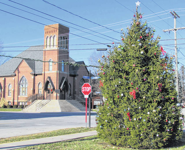 The Mowrystown Christmas tree is pictured Thursday. Mona Crone of Mona Lisa's Restaurant said that in previous years, folks would gather on the steps of the Presbyterian Church in the background to sing carols and hear a brief message about the true meaning of Christmas before Santa Claus would appear with a paper lunch sack of peanuts and fruit for each of the children.