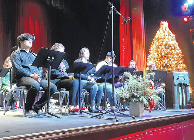 "With a Christmas tree and vintage console radio for effect, several of the cast are shown during the radio play ""Miracle on 34th Street"" at Bainbridge's Paxton Theatre."