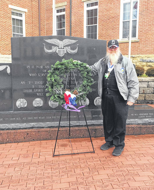 "Gerold ""Buzzard"" Wilkin is pictured placing a wreath at the Highland County Veterans Memorial in Hillsboro on Dec. 14 for the Highlanders Chapter of the Sons of American Revolution on National Wreaths Across America Day. Wilkin said the Highlanders put out a total of 43 wreaths. Originally composed of members from Highland, Adams and Brown counties, Wilkin said the Highlanders are in the process of allowing members from several surrounding counties."