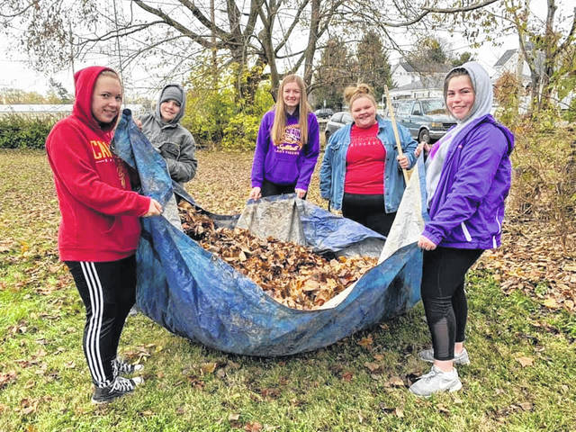 In a scene from November 2019, New Directions members do yard work at the Elizabeth's Hope Pregnancy Resources center in Greenfield.