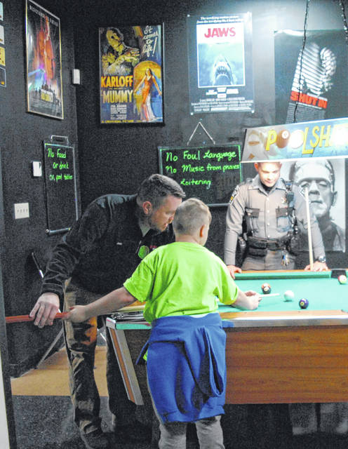 Two Brown County officers teach a Shop with a Cop mentee how to play pool at 24 Deli in Hillsboro.
