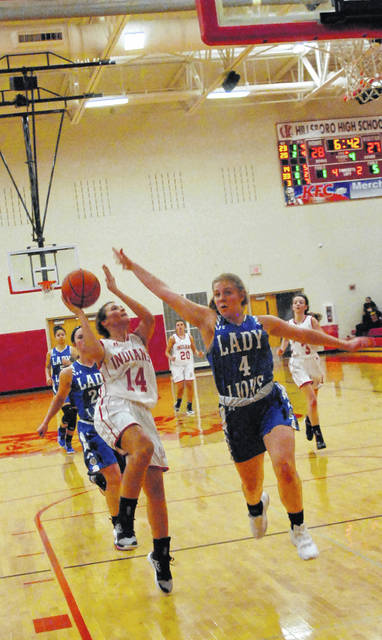 Lady Indians' Josie Hopkins going up for a layup with Kendell Dye in her face attempting to get a block shown in this photo.