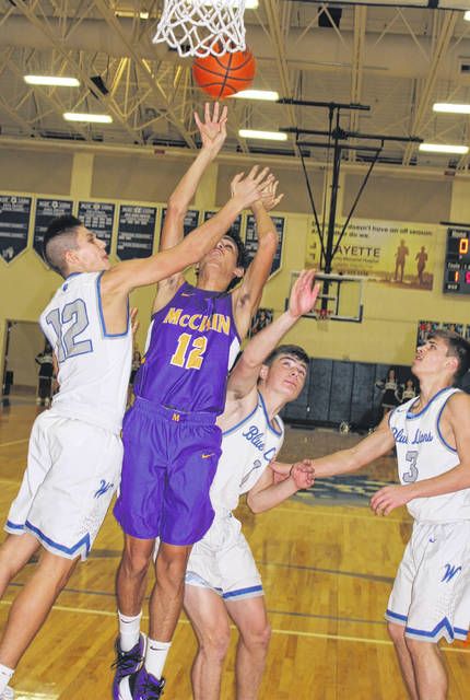 McClain junior Lyle White (12) puts up a shot during a Frontier Athletic Conference game at Washington High School Friday, Jan. 10, 2020. Blue Lions pictured (l-r); juniors Mitch Lotz and Brice Cartwright and sophomore Karson Runk.