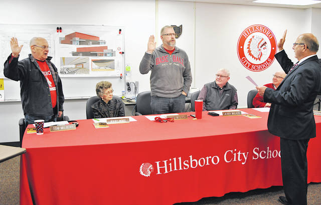 Tom Milbery, left, and Bill Myers are sworn in Monday after winning re-election in November to the Hillsboro City Schools Board of Education. Myers was also sworn in as the 2020 board president. Do the swearing in is school treasurer Ben Teeters. Also pictured, from left, are board members Beverly Rhoads, Jerry Walker and Larry Lyons.