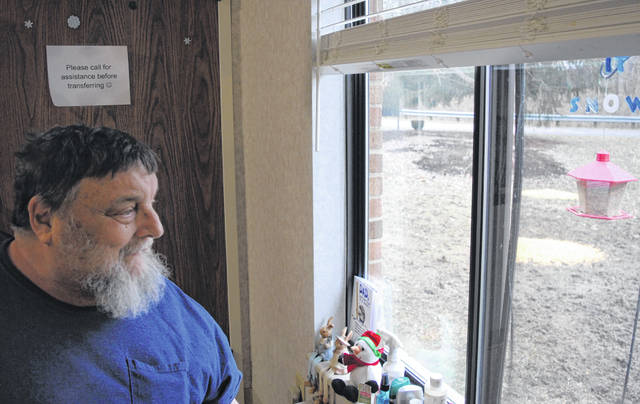 From his room at Heartland of Hillsboro, Homer Swift, a 65-year-old McClain High School alumnus, watches squirrels eat the corn his family and friends leave outside his window.