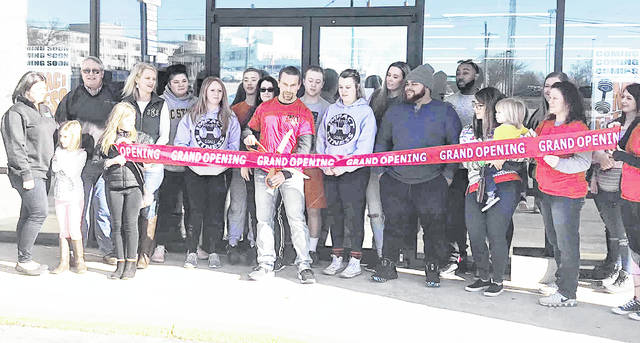 Tom Daniels, center, is pictured cutting a ribbon at the grand opening of Impact Fitness, located at 1260 N. High St. in Hillsboro.