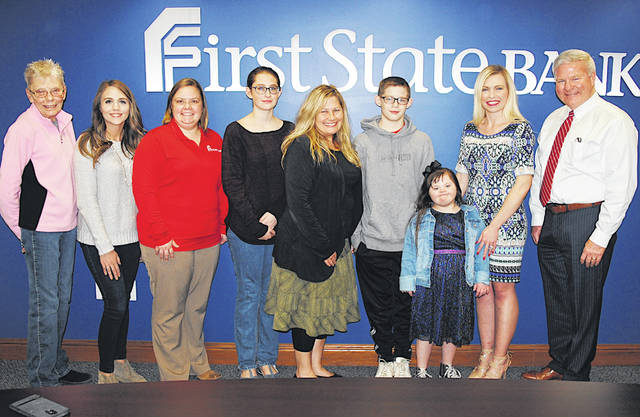 Elisha Duncan, third from right, the 2020 Highland County Society for Children and Adults poster child, is pictured Monday at First State Bank in Hillsboro. Also pictured is her mother, Kim O'Madden (center); siblings Isabella O'Madden and Isaiah Nussbaum (on each side of their mother); First State Bank President and CEO Mike Pell (far right); Gayle Coss, executive director of the society (far left); and First State employees Amy Hamilton, Diana Grooms and Lauren Hamilton.