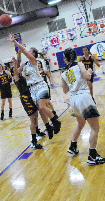 Lady Mustangs' Serena Smith going up for a layup against a Federal Hocking defender during Sectional Tournament game.