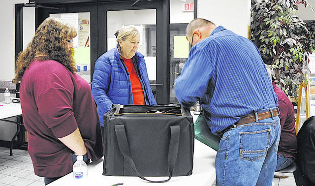 In a scene from the November 2019 election, poll workers Angie Mustard and Kathy Levo deliver ballots to the Highland County Board of Elections after polls closed. Pictured, from left, are Mustard, Levo and election volunteers Steve Cox and Tim Young (partially hidden).
