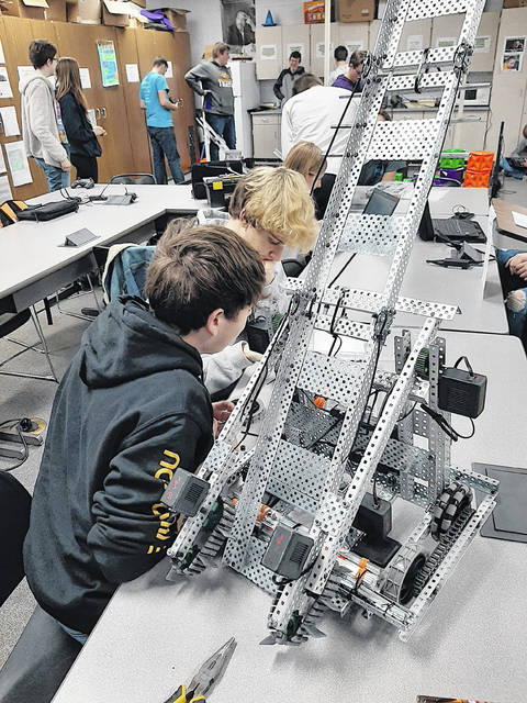 McClain High School students Garett George and Hayden Roll work on their robot.
