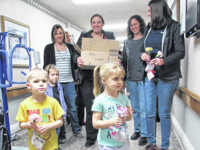 It may have been a rainy and chilly evening, but members of the Hillsboro Jr. Women's Club that included little Aiden Pniewski and his sister Olivia (front), brightened the mood at Heartland of Hillsboro Wednesday night by giving every resident a special Valentine's Day flower and vase, donated by Blossom's & Buds and Crowe Financial Group, LLC of Hillsboro. In the background are club members Brittane Dance with her daughter, Kinsley; Mary Boatman; Beth Pniewski; and Stacy Ashley.