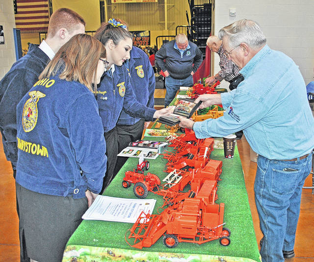 Jim Gorman, right, tells Highland County FFA students about the toy farm implements he makes and had on display at a past Highland County Chamber of Commerce Ag is Everyone's Business event at Southern State Community College in Hillsboro.