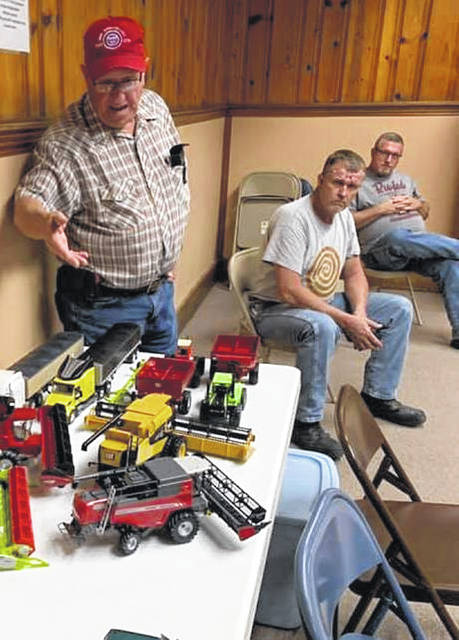In a scene from the Southwestern Ohio Farm Toy Collector Club's October meeting, Gary Neu gestures at a cluster of farm toys. Pictured, from left, are Gary Neu, Henry Hall and Gary Arledge.
