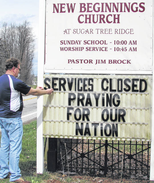 The Rev. Jim Brock is pictured Friday at the New Beginnings Church in Sugar Tree Ridge, finishing the lettering on a side outside the church.