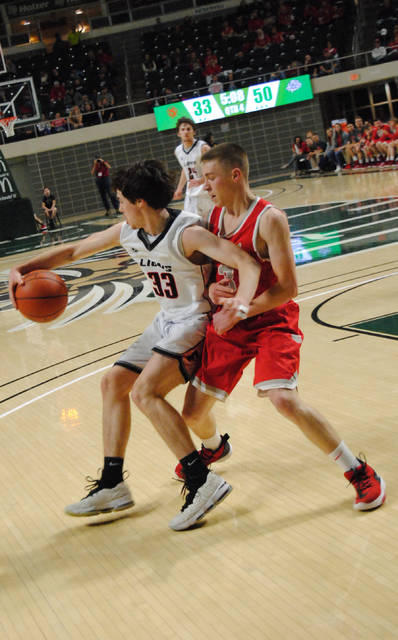Senior Bryson Simmons for the Fairfield Lions attempting to spin past Trimble defender to go up for a layup.