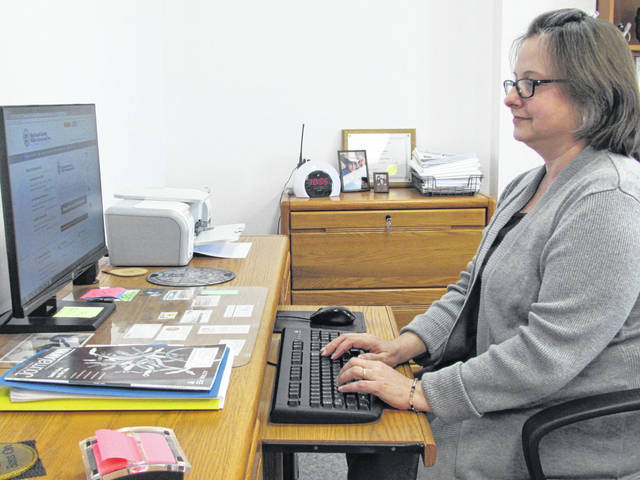 Hattie Lovedahl, general manager of the Highland County Water Company, sits at her desk reviewing operations at the utility.