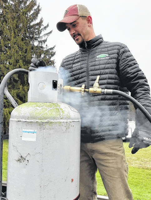 Jeremiah Riggs, an employee of Sherwood Auto & Camper Sales in Hillsboro, fills a propane tank for a customer.