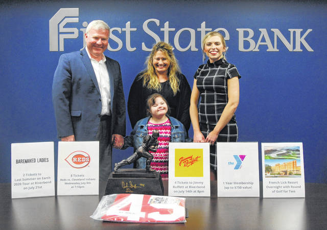 Elisha Duncan, the 2020 Highland County Society for Children and Adults Poster Child, and her mother pose with auction items for the Ernie Blankenship Radio-Telethon. The telethon will be held on March 25 from 7-9 p.m. at the Hillsboro Orpheum and McClain High School TV studio in Greenfield. Pictured, from left, are First State Bank President and CEO Michael Pell, Elisha Duncan, Kim O'Madden, and First State Bank's Hillsboro Banking Center Manager Diana Grooms.
