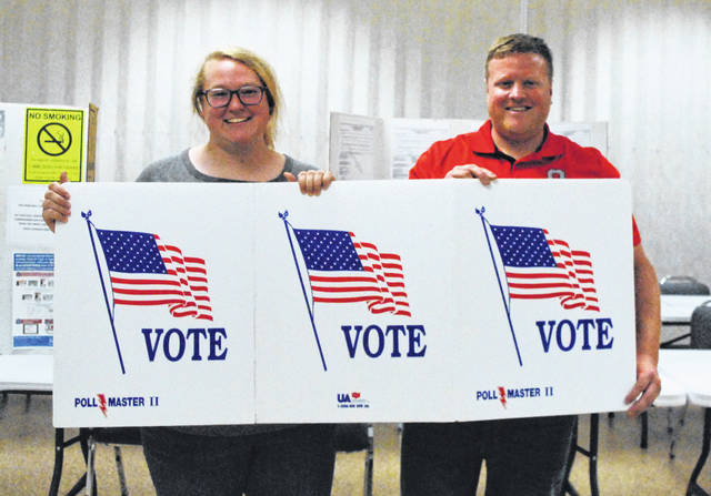 During an October 2019 open house, Highland County Board of Elections office clerk Casey Clark, right, and poll worker Ryan Starks encourage residents to vote.
