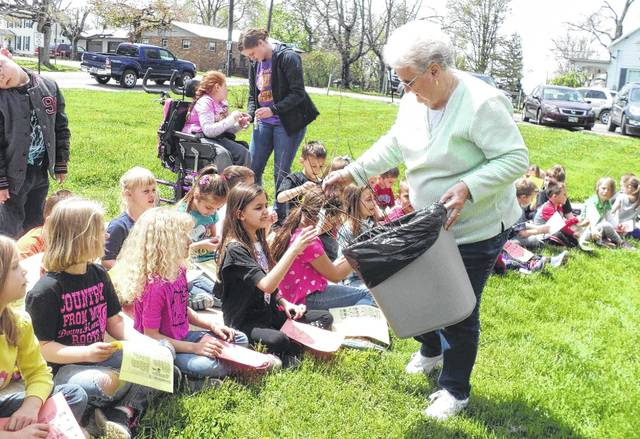 In a scene from Arbor Day 2015, then-Greenfield Council Chair and Village of Greenfield Tree Commission member Betty Jackman presents Buckskin first-graders with redbud seedlings.