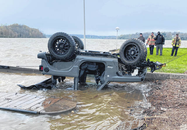 Officials look on Wednesday as a Jeep Wrangler is pulled from Rocky Fork Lake at the Fisherman's Wharf area. The Paint Creek divers were Keith Giffin and Cameron Clouser.