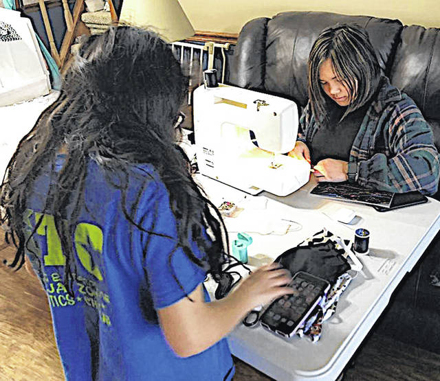 Sisters Kyah and Jayah Chaney are pictured making masks to protect local residents against the COVID-19 pandemic.