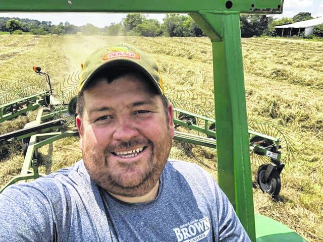Nathan Brown, pictured raking hay at his Hillsboro area farm, says farmers are seeing weather patterns similar to the ones that plagued them a year ago.