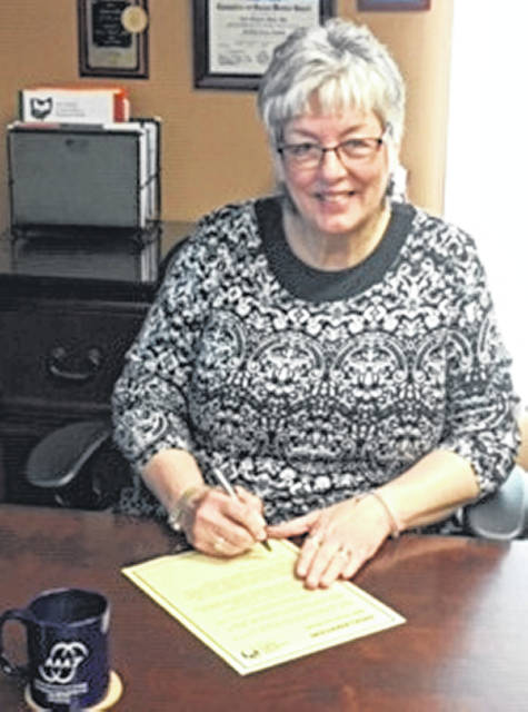 Nina R. Keller, executive director of the Area Agency on Aging District 7, signs a proclamation for Older Americans Month that is observed each May.