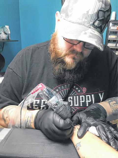 In a pre-COVID-19 scene, Olde Town Ink owner Brian Lansing tattoos a client.