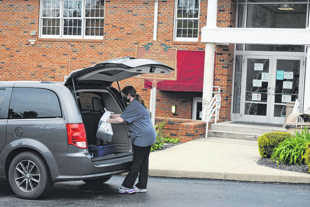 Librarian Emily Foster places requested library items into a patron's vehicle at the Hillsboro Public Library. All Highland County libraries opened for curbside service on Monday.