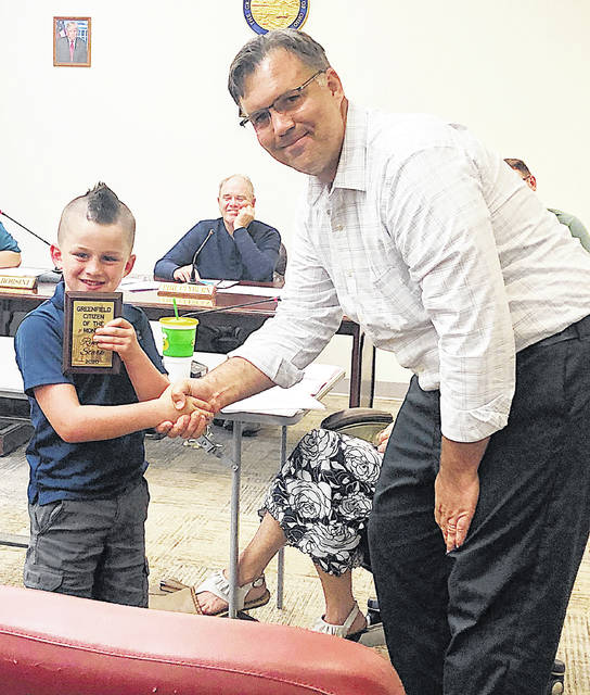 Greenfield City Manager Todd Wilkin presents Ryker Stark with the village's first Citizen of the Month Award at Tuesday's council meeting.