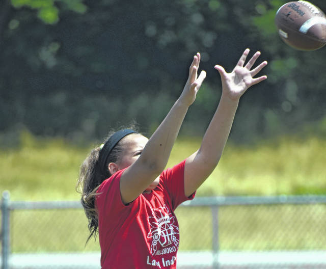 Annia Young preparing to catch the football during Friday afternoon workouts at the youth football field at Liberty Park.