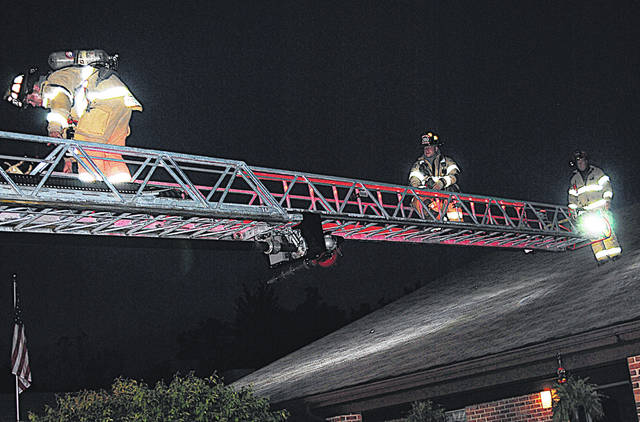 Firefighters work from a ladder to check things out Thursday evening at Heartland of Hillsboro.