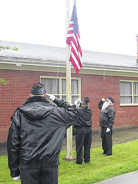 Highland County Veterans Honor Guard members, from left, James Vinson, Rick Edison and Gary Cruea raise a new flag Sunday at the Hillsboro Elks.