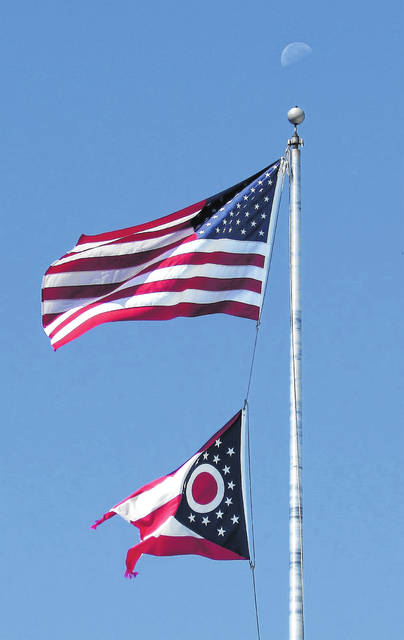 As a half-moon hovers above the flag pole at the Fraternal Order of Eagles lodge in Hillsboro, the Ohio flag and Stars and Stripes fly against a clear blue sky Friday morning.