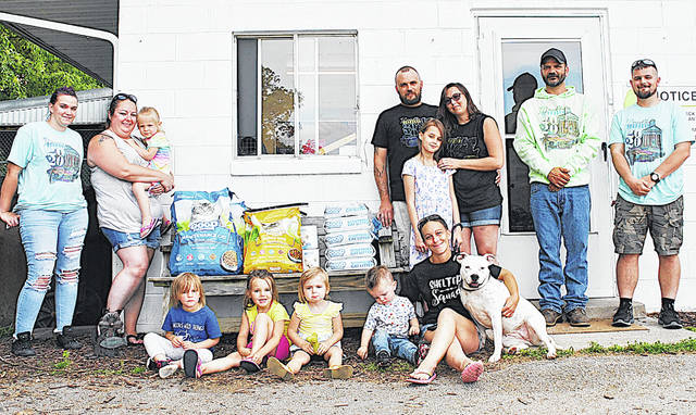 The Highland County Humane Society Animal Shelter received a check for $300, a $100 gift card to Rural King and $100 worth of food and litter Tuesday from organizers of recent Bring Back Cruising in Hillsboro events. Pictured are staff members and their children from the shelter and the cruising events (from left) Jada Miller, Melissa Davis holding Lydia Davis, Hailey Miller, Maci Walker, Eliyanah Hopkins, Lincoln Miller, Rob Hopkins, Braelynn Hopkins, Megan Wolf (seated), Surina Deeter, Dan Holsinger and Wesley Miller. The group is pictured at the animal shelter on SR 124 east of Hillsboro with some of the donated items.