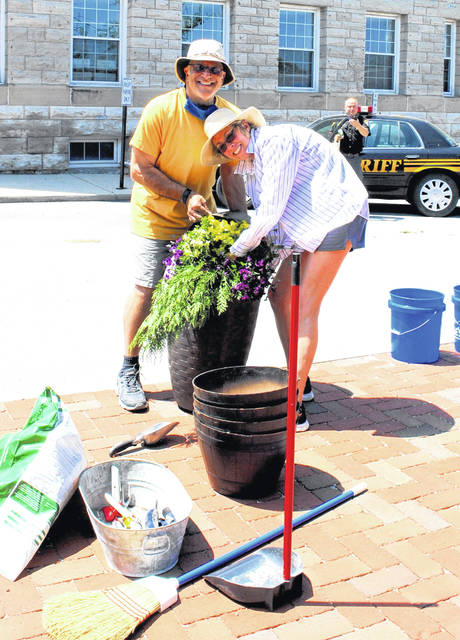 In uptown Hillsboro on Tuesday, volunteers Charlie Guarino, left, and Karen Trout, right, repot flowers donated to the city of Hillsboro by local resident Buck Wilkin. The couple celebrated Trout's birthday on Sunday, their wedding anniversary on Monday, and Guarino's birthday on Tuesday.