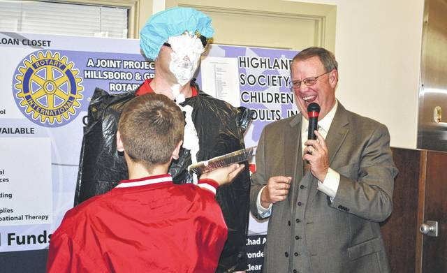 In a scene from the 2014 radio-telethon, emcee Rick Williams, right, looks on as Hillsboro Elementary Principal Jacob Zink takes a pie in the face from student Hunter Green after the school exceeded its fundraising goal. Schools, businesses and others often compete in challenges to raise money for the event.