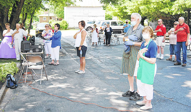 Local residents hold their hands over their hearts during a Fourth of July celebration Saturday at the Highland County Historical Society's Highland House Museum in Hillsboro.