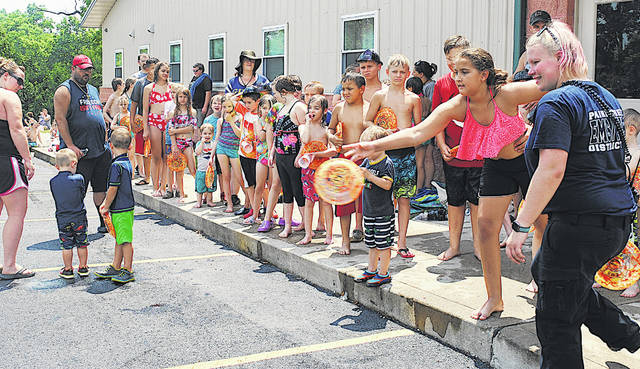Kids line up to play a game with a chance to win a free Kona Ice shaved ice treat during a Water Day held Friday by the Paint Creek Joint EMS/Fire District at its Hillsboro location. Paint Creek gave away free frisbees and plastic fireman helmets. Sarah Lott (far right), the public education outreach coordinator for Paint Creek, directs kids in how to play the game. Paint Creek Lt. Brandon Jackman said Kona Ice gave them a bunch of free tickets for shaved ice treats, so they decided to have a game to see which kids would get the tickets. Friday's was the third Water Day Paint Creek has provided this summer. The fourth and final one will be held from 11 a.m. to 1 p.m. Friday, July 24 in Greenfield.