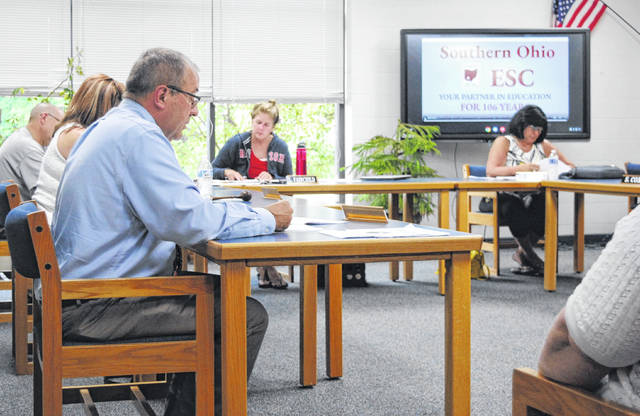During the Bright Local School Board meeting, superintendent Mike Bick (foreground, left) reads his recommendations for reopening school on Wednesday, Aug. 19.