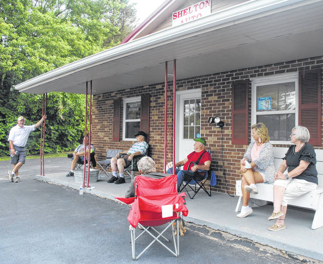 """Last month, Shelton Auto Sales owner Joe Shelton decided to host """"old dogs meetings,"""" where people could stop by and reminisce. Pictured, from background to foreground: Joe Shelton, Don Tumbleson, Larry Hedges, Tom Ross, Jenny Shelton, Don Carey (seated in the red chair and facing away from the camera), Diana Carey."""