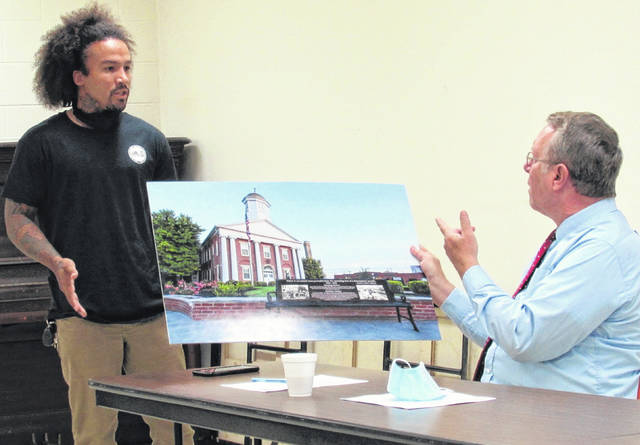 Shawn Captain (left) describes his computer rendering of a memorial tribute bench planned for the Highland County Courthouse square to commissioner Gary Abernathy.