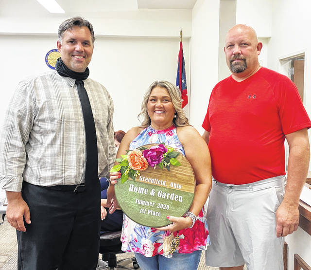 Carl and Amy Storer are pictured with Greenfield City Manager Todd Wilkin (far left) at Tuesday's council meeting where they were presented with Greenfield's Home and Garden Award. They are pictured with the door-hanger award, which was made by Susan Howland.