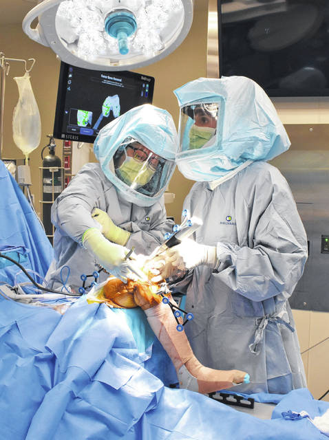 Dr. Alex Renshaw, orthopedic surgeon of Highland Advanced Orthopedics & Sports Medicine, assisted by Deidre Slater, surgical rirst assist, performs the first hand-held, robotics-assisted total knee arthroplasty in the region at Highland District Hospital.