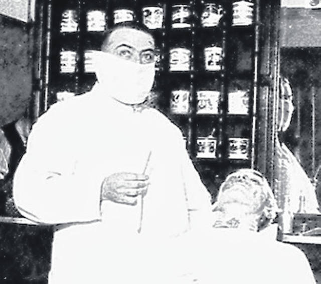 This picture courtesy of the History Channel website shows a Cincinnati barber wearing a mask during the 1918 pandemic.