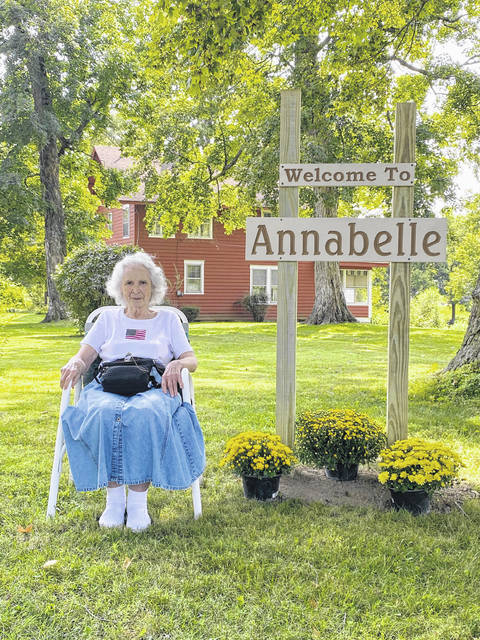 Annabelle Peabody, who called the house behind her home for 56 years, is pictured by a sign marking the property's new name, a tribute to her from the new owner.