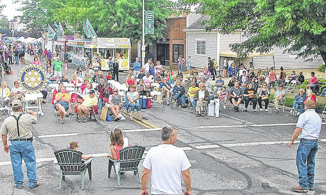 In a scene from a past Greenfield Rotary Club Auction held at the Greene Countrie Towne Festival, auctioneers in the foreground entice a gathered crowd to bid.